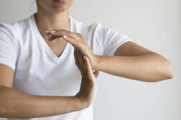 Woman holding wrist.